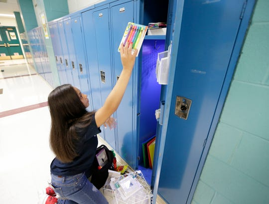 Sonia Rivas, a sophomore, organizes her locker at Golda Meir School in Milwaukee on Monday.
