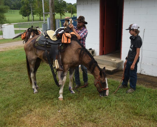 C.J. Garton and his 13-year-old son, Clinton, pack up their horse Pancho before riding from Mountain Home to the Cotter/Flippin area Sunday afternoon. The Gartons are riding from Nashville, Tenn., to Depew, Okla., to raise awareness for traditional country music.