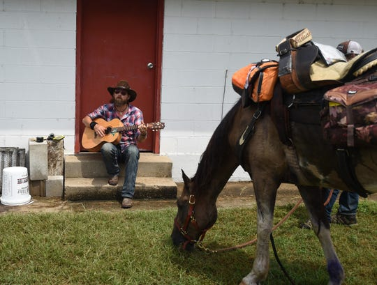 "Country artist C.J. Garton performs the song ""The Hanging"" while Pancho the horse snacks on the grass at the Saddle Club Arena in Mountain Home on Sunday afternoon. C.J. Garton and his son, Clinton, are riding from Nashville, Tenn., to Depew, Okla., to raise awareness about traditional country music."