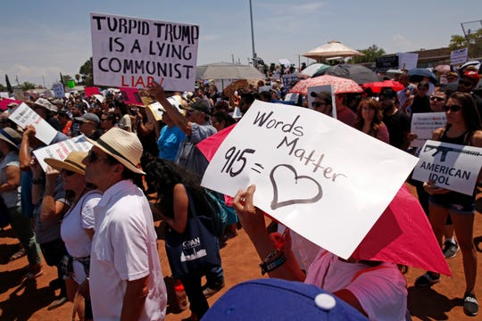 Demonstrators hold signs to protest the visit of President Donald Trump to the border city after the Aug. 3 mass shooting in El Paso, Texas, Wednesday, Aug. 7, 2019. Aiming to play the traditional role of healer during national tragedy, President Donald Trump paid visits Wednesday to cities reeling from the mass shootings. (AP Photo/Andres Leighton)