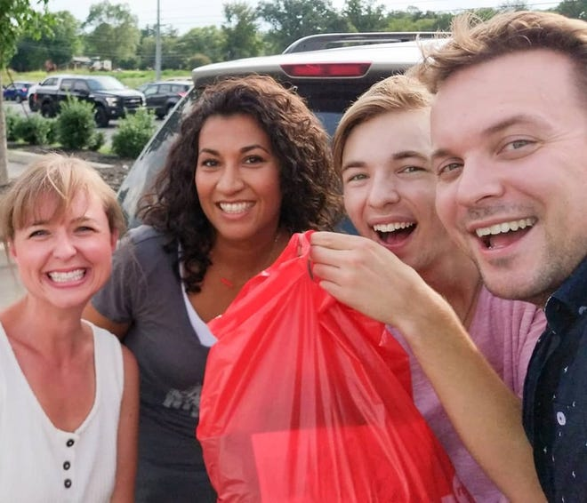 Leslie Roberts, second from left, returned a missing bag of clothes to the Andrews family, from left, Caroline, Ewan and Tyler Andrews.