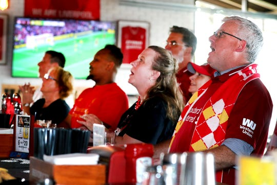 Laura Marren, left and her husband Greg Marren, right members of Liverpool Football Club Murfreesboro TN fan club cheer on Liverpool with other members at the Murfreesboro Party Fowl as they watch a game against Norwich on Friday Aug. 9, 2019.