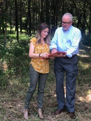 Refuge Center for Counseling director Amy Alexander and Keith Solomon from Lenders Title Company go over the contract for the purchase of the land.
