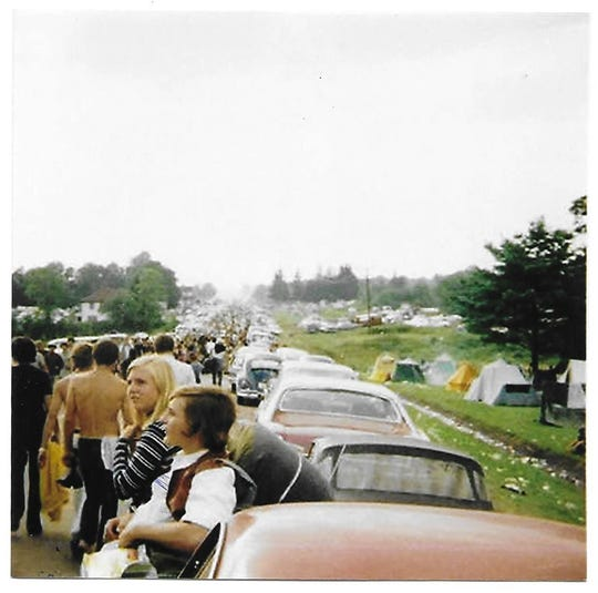 Casey Wolff of Naples, six friends and thousands of others walk along a road toward the Woodstock music festival in New York in August 1969.
