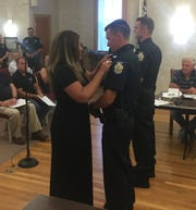 Officer Cade Risch receives his badge from his mother, Heather.