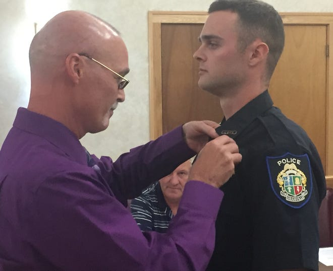 Officer Dakota Spires receives his badge from his father, Jeff, on Aug. 7.
