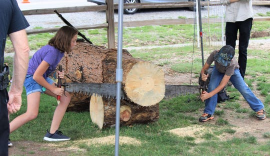 These two youth learns that it takes teamwork to use a blade saw at the 75th Smokey Bear celebration.