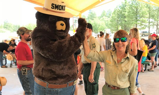Smokey Bear and Jodie Canfield, of the Lincoln National Forest Ranger District, high fives at a 75 year extravaganza for the bruin.
