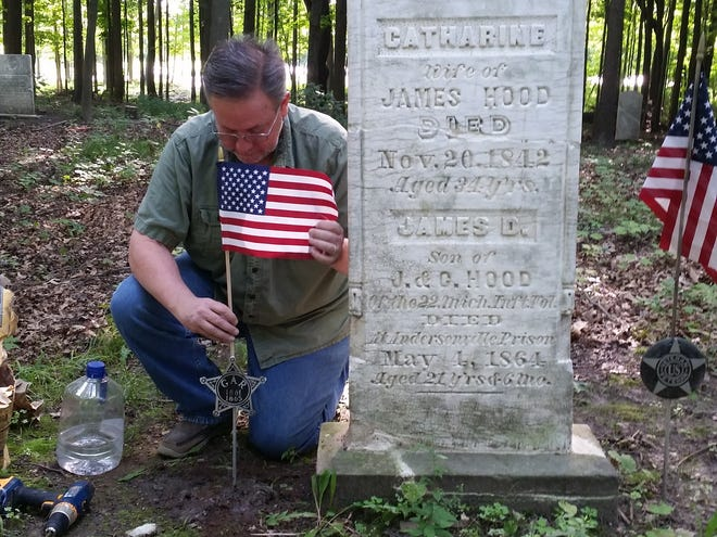 Mike Tavarozzi places a flag at a a gravestone for the Hood family in Olds Cemetery. James D. Hood was a Union soldier from Lyon Township who died during the Civil War and is being honored.