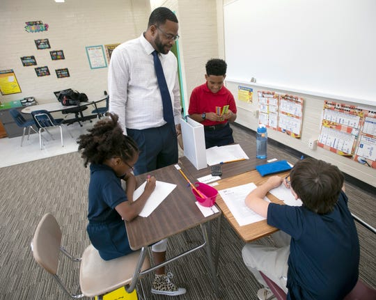 Fifth-grade teacher Kenyon Moody talks with a group of new students on the first day of school at the Dixon School of Arts and Sciences.