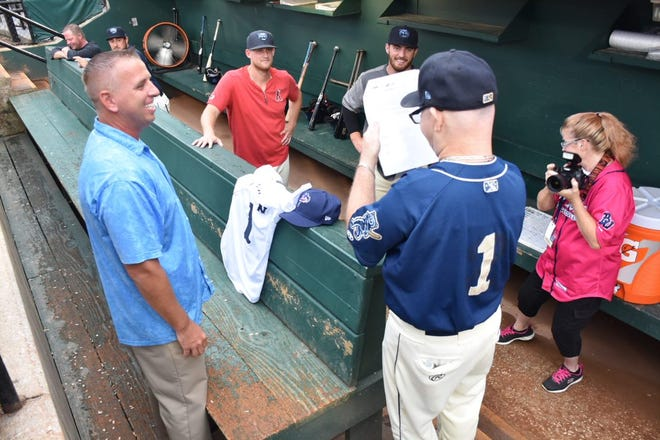 Mobile BayBears players cheer on batboy Wade Vadakin as he looks over and signs the Blue Wahoos employee contract to join team. Vadakin was elected to the Southern League Hall of Fame.