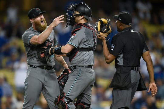 Arizona Diamondbacks relief pitcher Archie Bradley (25) yells to the Los Angeles Dodgers dugout after the game next to catcher Carson Kelly (18) at Dodger Stadium.