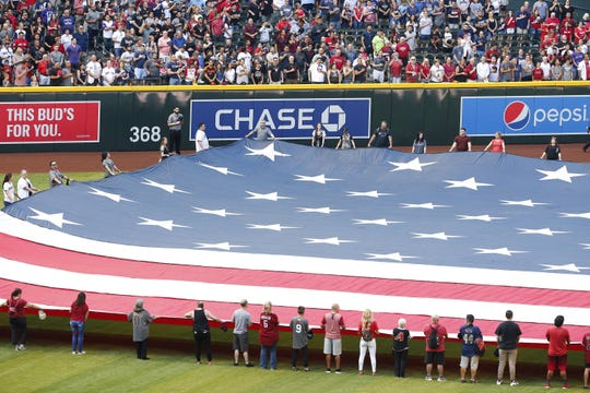 Arizona Diamondbacks fans hold the flag during the National Anthem on Opening Day at Chase Field in Phoenix on April 5, 2019.