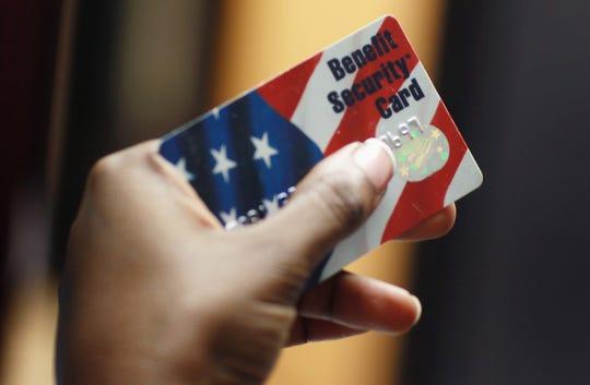 Una persona sostiene en su mano una tarjeta, con la que se le permite hacer uso de estampillas de comida.