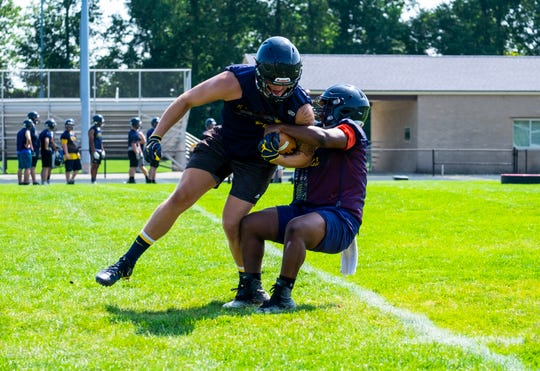 Port Huron Northern tight end Braiden McGregor, left, and linebacker John Young run a drill during the team's first practice Monday, Aug. 12, 2019, at Port Huron Northern High School.