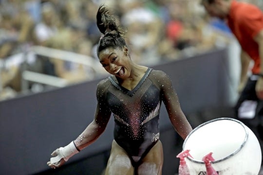 Simone Biles celebrates after completing the uneven bars to win the all-around title during the senior women's competition at the 2019 U.S. Gymnastics Championships Sunday, Aug. 11, 2019, in Kansas City, Mo. (AP Photo/Charlie Riedel)