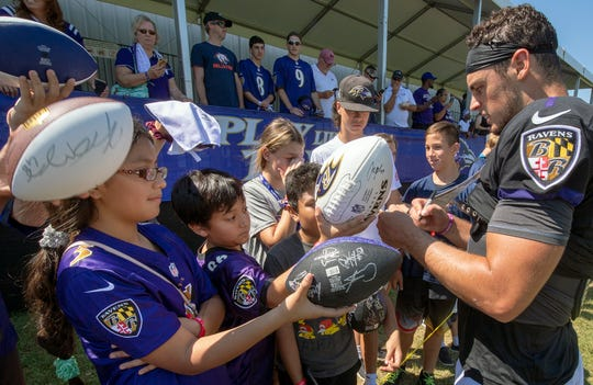 Trace McSorley signs autographs for fans during Ravens training camp in Owings Mills, Maryland.