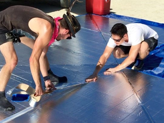 Andrew Mitchell of Los Angeles lays down tape while fellow first-time Burning Man participant Jeremy Wisuthseriwong of San Francisco smooths it out. The two bought building insulation from a home improvement store and learned how to make their shelter by watching YouTube videos.