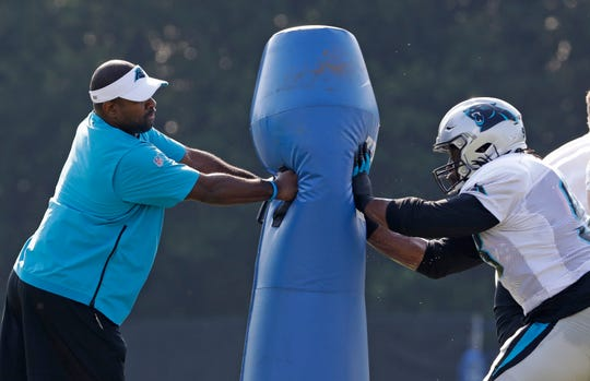 Carolina Panthers defensive line coach Sam Mills III, left, runs a drill with Gerald McCoy, right, during practice at the NFL football team's training camp in Spartanburg, S.C., Monday, July 29, 2019. The Buffalo Bills will practice with the Panthers on Tuesday and Wednesday.