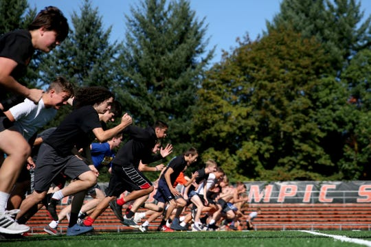 Football players run sprints at a practice before the season starts at Sprague High School in Salem on Aug. 12, 2019.