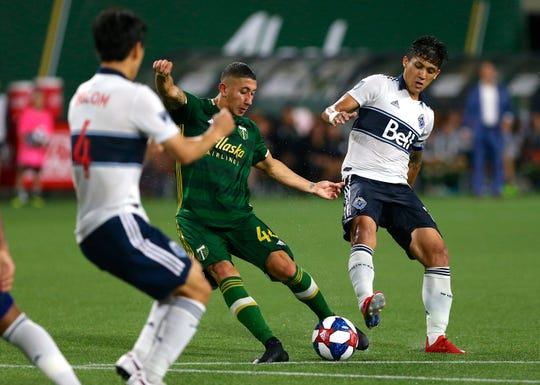 Portland Timbers' Marvin Loria attempts a shot on goal between Vancouver Whitecaps players, including Inbeom Hwang, left, during an MLS soccer match Saturday, Aug. 10, 2019, in Portland, Ore.