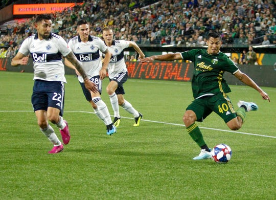 Portland Timbers' Renzo Zambrano shoots as Vancouver Whitecaps, including Erik Gody (22) and Jake Nerwinski (28), defend during an MLS soccer match Saturday, Aug. 10, 2019, in Portland, Ore.