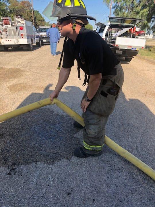 A San Angelo fireman helps move the hose during the blaze on E. 40th street.