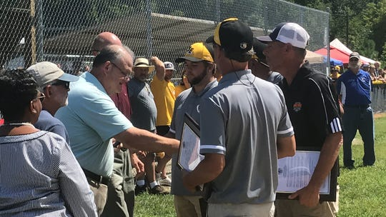Members of the Accomack County Board of Supervisors congratulate coaches for the Boys Senior League Southeast Region champion team during a celebration in Onancock, Virginia on Sunday, Aug. 11, 2019. The team went on to place fourth in the nation at the Senior League Baseball World Series.
