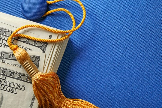 A stack of one hundred dollar bills on top of a blue graduation cap.  A gold graduation tassel is draped over the stack of money. The ledft side of image is available for copy.