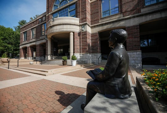 A statue sits on a bench reading a book outside of F.W. Olin Library on the campus of Drury University in Springfield, Mo.