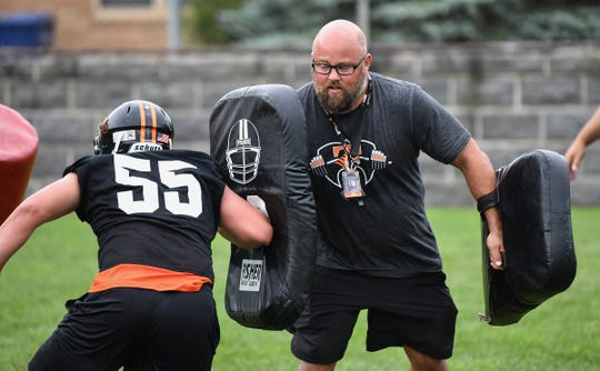 Tech head coach Jon Benson works with his players during the first day of practice Monday, Aug. 12, 2019, at Clark Field in St. Cloud.