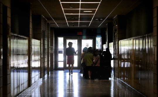 A teacher leads her students down a hallway to their classroom at Talahi Community School in St. Cloud in this file photo.