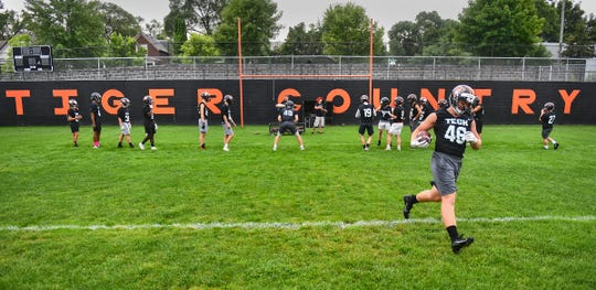 Tech players take the field for the first football practice of the season Monday, Aug. 12, at Clark Field in St. Cloud.
