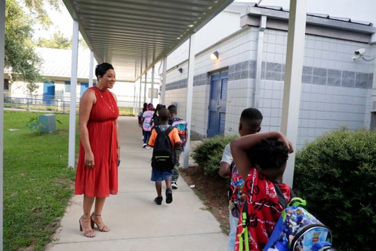 Pineview Elementary School principal Carmen Conner greets students on their way to class on the first day of school Monday, August 12, 2019.