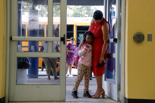 Pineview Elementary School Principal Carmen Conner hugs second grader Erica Bradham, 7, as she gets off the bus on the first day of school Monday, August 12, 2019.