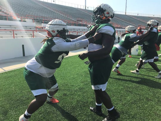 FAMU defensive tackle Jacques Penney (left) works on his balance in getting underneath the shoulder pads during practice.