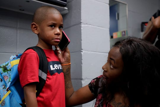Jayden Hannan, 5, apprehensive about leaving his mother, Dee Ford, on his first day of kindergarten at Pineview Elementary School, hears words of encouragement from his father on the phone Monday, August 12, 2019.