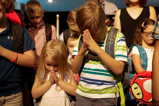 Siblings Emily, 4, left and Ben, 7, young members of the Killearn United Methodist Church congregation, bow their heads in prayer during the church's annual blessing of the backpacks Sunday, August 11, 2019.