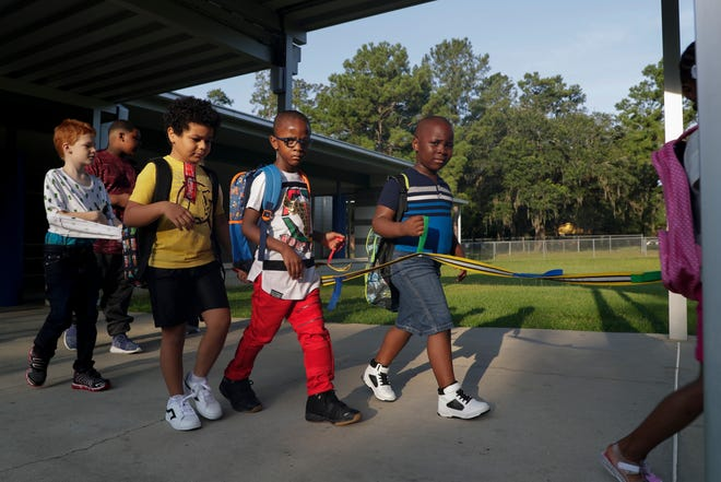 Students in Miss Everett's Pineview Elementary class walk to their classroom on the first day of school Monday, August 12, 2019.