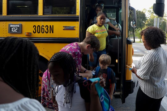 Students arrive off the bus on the first day of school at Pineview Elementary Monday, August 12, 2019.