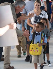 St. Lucie County school Superintendent E. Wayne Gent greets Rivers Edge Elementary School first grader Jordan Acosta, 6, of Port St. Lucie, on the first day of school Aug. 12. The school district received a grant to help teachers pursue graduate degrees to become school mental-health professionals.
