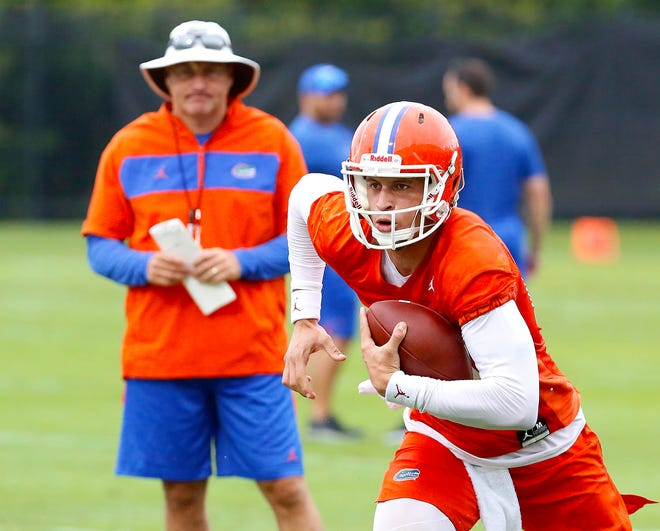In this July 26, 2019, file photo, Florida quarterback Feleipe Franks (13) runs with the ball as head coach Dan Mullen watches during an NCAA college football practice in Gainesville, Fla.