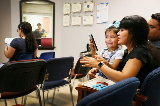 Carla Naranjo, 4, plays with her mom's phone while waiting to get her measles shot Thursday, Aug. 1, 2019, at the El Paso Department of Public Health. Beatriz Naranjo and her husband, Sergio Naranjo, took their daughter in to get her measles shot before the start of the school year.