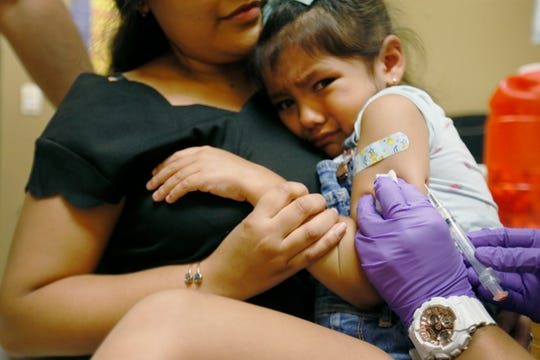 Carla Naranjo, 4, cries while holding on to her mom Beatriz as she gets her measles shot Thursday, Aug. 1, 2019, at the El Paso Department of Public Health.