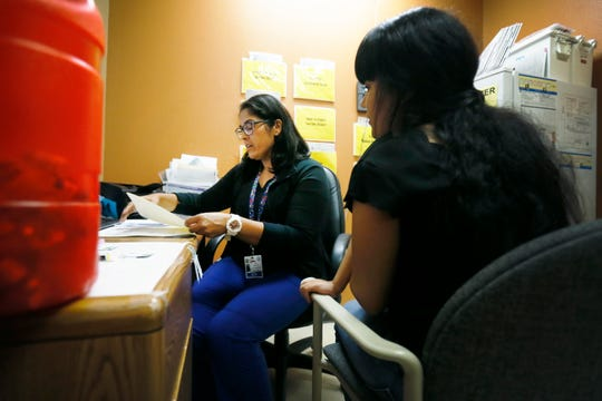 Nurse Amira Awad talks to Beatriz Naranjo before giving her daughter, Carla, her measles shot Thursday, Aug. 1, 2019, at the El Paso Department of Public Health.