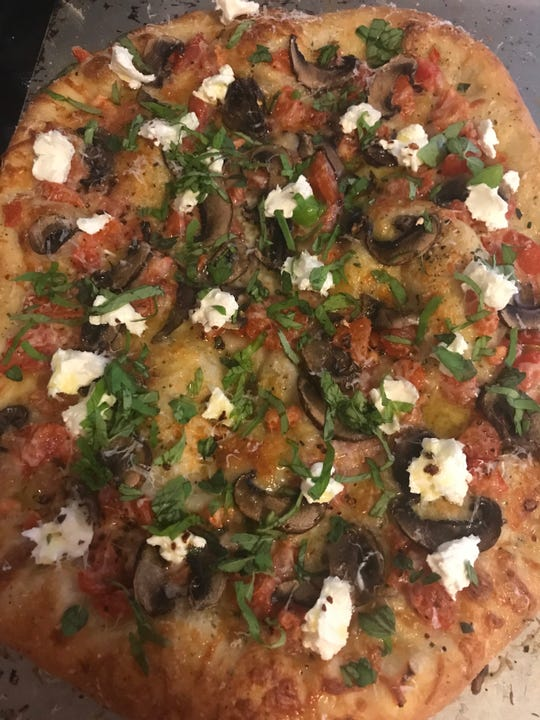 A mushroom-tomato pizza made at home with dough from Serpe's Bakery. Bake it at 450 degrees for about 10 to 12 minutes. We topped it with goat cheese and fresh basil when it came out of the oven and drizzles of olive oil.