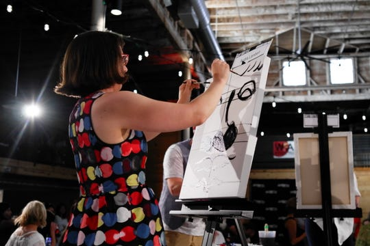 Audra Lambert will do a short demonstration from 5:15 to 5:45 p.m. Saturday at Art Battle Wichita Falls at the Warehouse of painting with two brushes at the same time. This image shows her doing that at the first Art Battle.