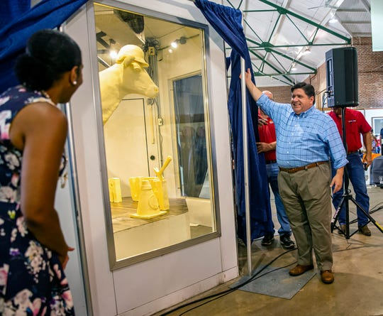 "Illinois Gov. JB Pritzker, center, and Illinois Lt. Gov. Juliana Stratton, left, unveil the 2019 Illinois State Fair Butter Cow during a ceremony inside the Dairy Building on the Illinois State Fairgrounds, Wednesday, Aug. 7, 2019, in Springfield, Ill. The theme of this year's butter cow, made of 800 pounds of recycled butter by artist Sarah Pratt, is ""Building Our Future"" and contains nine hearts hidden within the sculpture that represent the essential nutrients found in dairy products."
