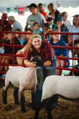 Liz Wetzel is all smiles as she leads her lamb in front of the judge in the show ring.