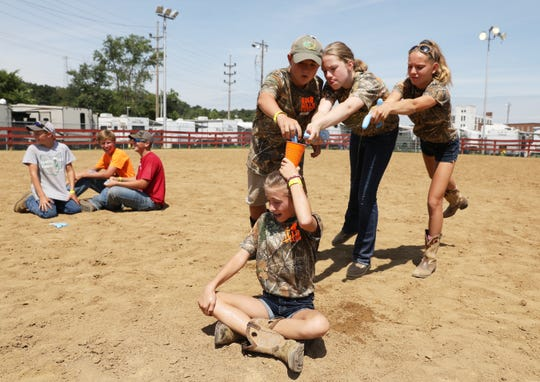 Michael Coen, left, Natalie Mallett and Hannah Chaney try to fill a cup perched on teammate Liza Neptune's head during the Farm Chore Olympics at the Muskingum County Fair on Monday. At left, The I Think Its Fine team celebrates their victory in the event, which featured a sack race, egg hunt and a competition to pick up paper plates and Frisbees with rakes.